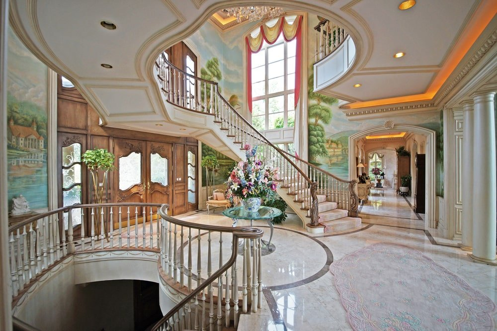 Upon entry of the house, you are welcomed by this foyer with bright walls, floor and tall ceiling paired with large windows and an indoor balcony. Image courtesy of Toptenrealestatedeals.com.
