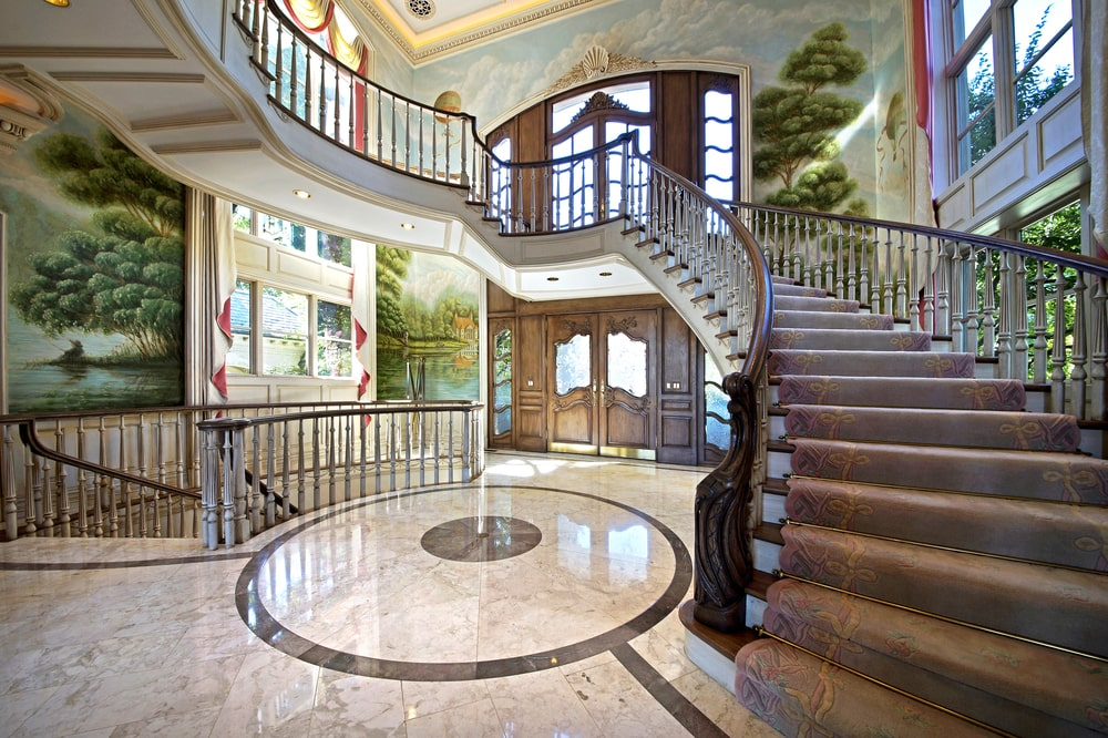 This other look at the grand foyer showcases the staircase railings and door frames that stand out against the beige walls and floor. Image courtesy of Toptenrealestatedeals.com.