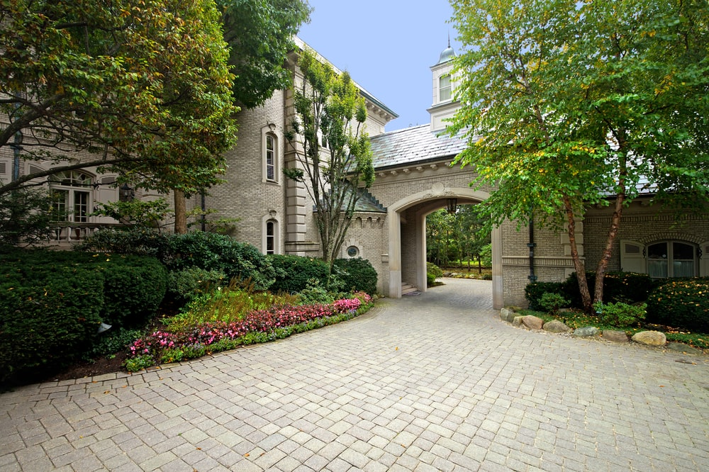 This is a close look at the main entrance of the front of the house with a large arch and a covered entryway adorned with a colorful garden on the side. Image courtesy of Toptenrealestatedeals.com.