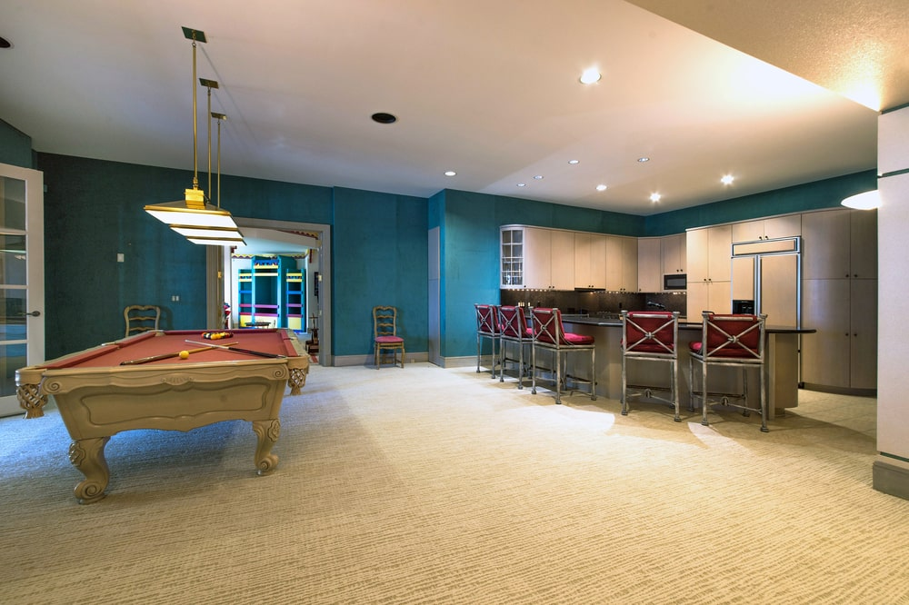 The house's game room has a pool table on one side and a bar on the other side. These are complemented by the green walls. Image courtesy of Toptenrealestatedeals.com.