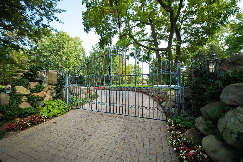 This is a look at the property from the vantage of the main gate. You can see here the large wrought-iron gate paired with tall trees and flowering shrubs. Image courtesy of Toptenrealestatedeals.com.