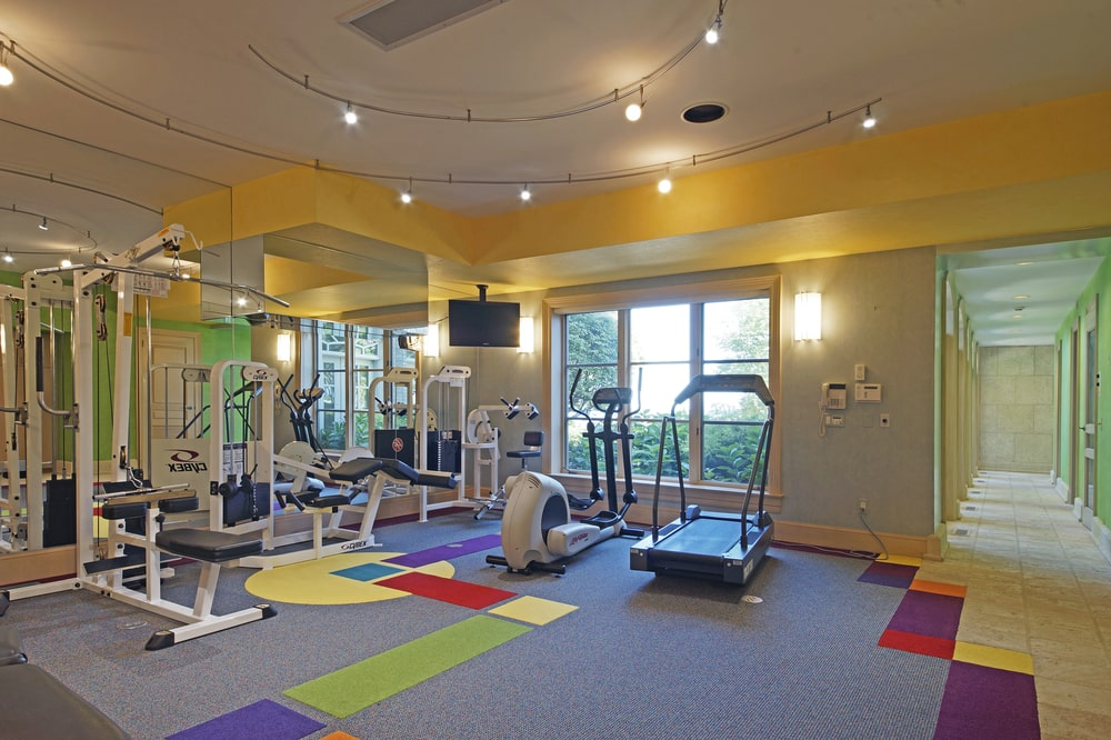 This is a look at the well-equipped home gym with brilliant lighting and beige walls. Image courtesy of Toptenrealestatedeals.com.