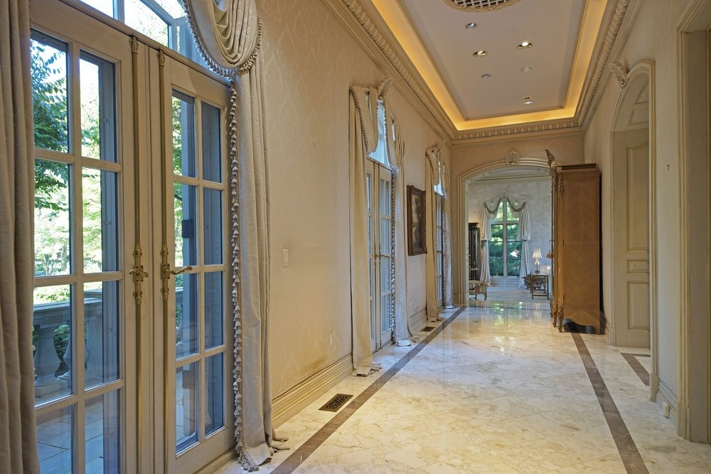 This hallway is lined with French glass doors on one side and topped iwth a beige tray ceiling with lighting. Image courtesy of Toptenrealestatedeals.com.