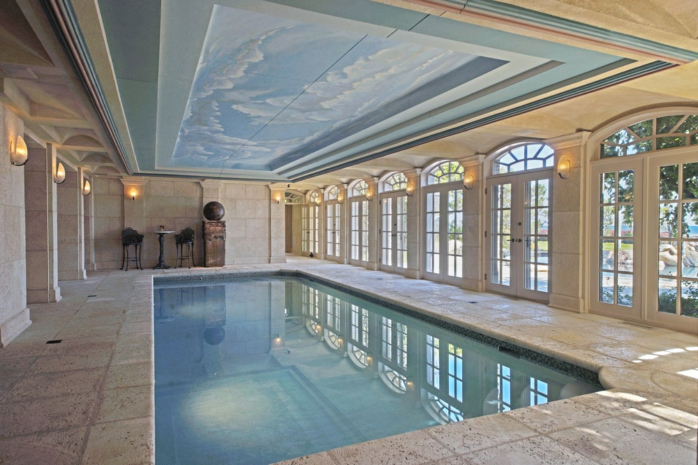 This is the indoor pool that is illuminated by the row of French glass doors on one side and adorned with a blue tray ceiling. Image courtesy of Toptenrealestatedeals.com.