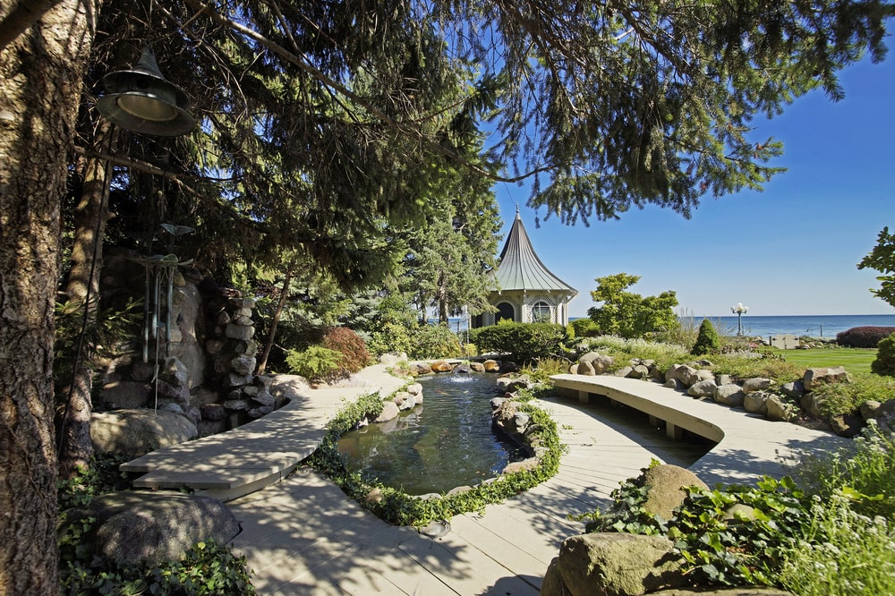 This is a look at the koi pond adorned with shrubs and a built-in concrete bench on the side. Image courtesy of Toptenrealestatedeals.com.