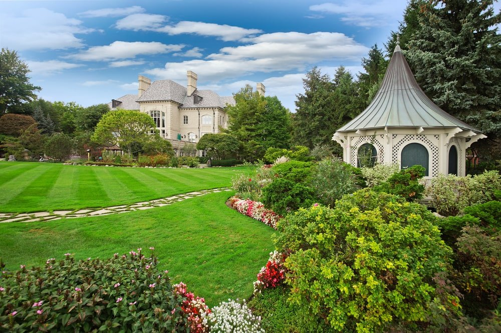 The landscaping that surrounds the house is filled with grass lawns, colorful shrubs and tall trees. Image courtesy of Toptenrealestatedeals.com.
