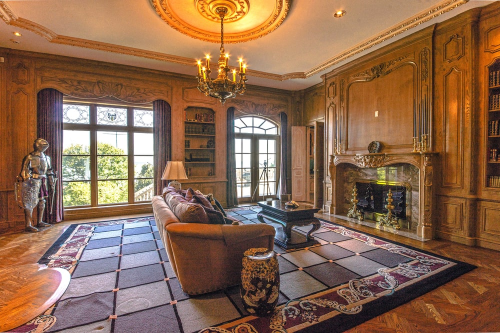 This is the spacious library with a large patterned area rug, a sofa and a large fireplace across from it. Image courtesy of Toptenrealestatedeals.com.