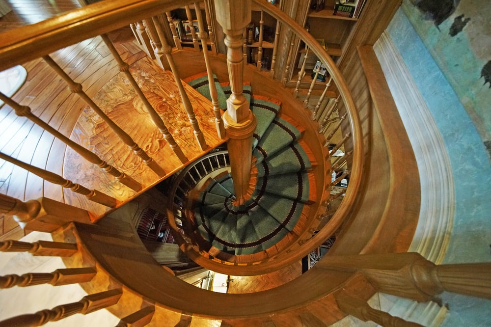 This is the spiral staircase of the library with wooden banisters and railings. Image courtesy of Toptenrealestatedeals.com.