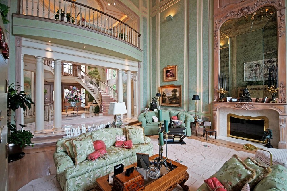This is the large living room with soaring ceiling, a fireplace topped with a large mirror and a sofa set that matches the walls. Image courtesy of Toptenrealestatedeals.com.