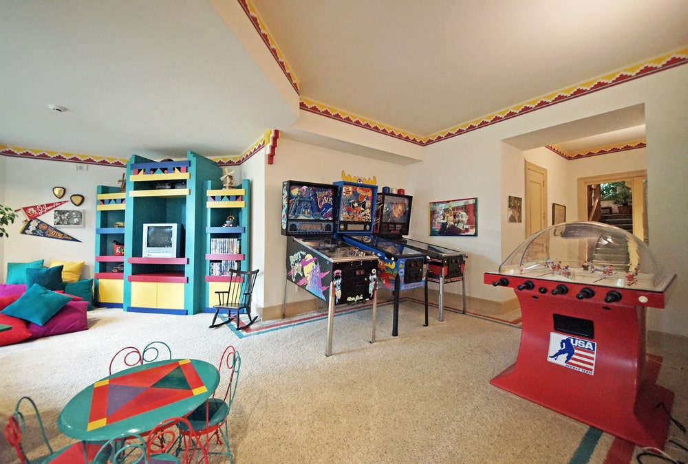 The colorful playroom has children's games, colorful cabinets and a small table set. Image courtesy of Toptenrealestatedeals.com.