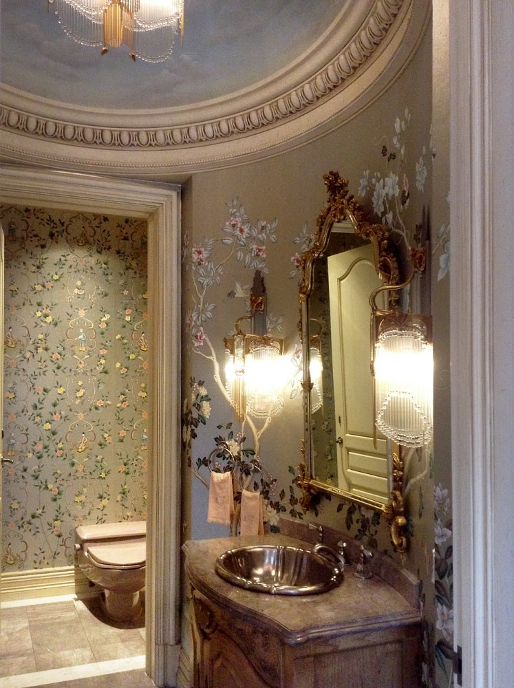 This is the powder room with floral patterns on its curved walls adorned with sconces. Image courtesy of Toptenrealestatedeals.com.