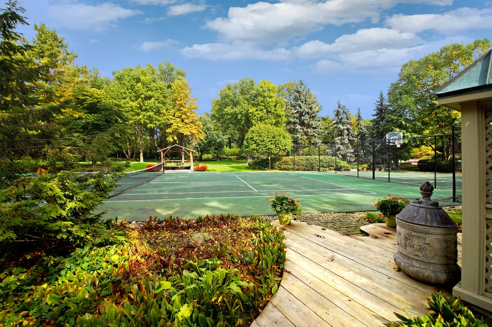 This is the large tennis court surrounded by tall trees and colorful shrubs. Image courtesy of Toptenrealestatedeals.com.