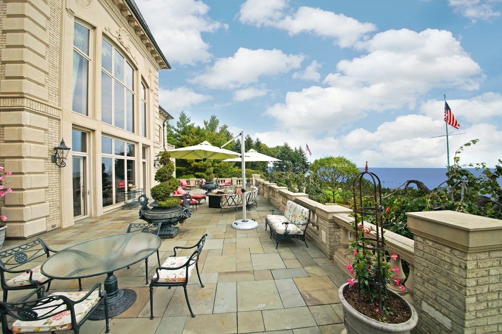 This is the veranda with an outdoor dining area and sitting area that has a view of the lake. Image courtesy of Toptenrealestatedeals.com.