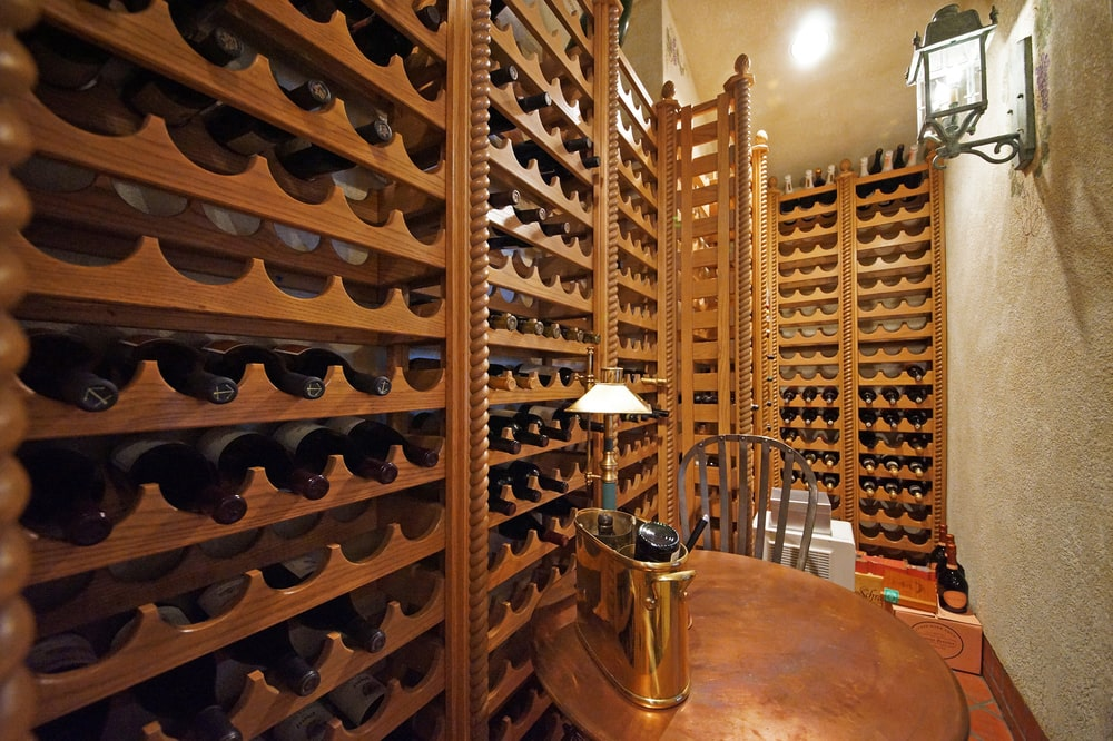 This is the wine cellar with built-in wooden bottle storage structures and a tasting area. Image courtesy of Toptenrealestatedeals.com.