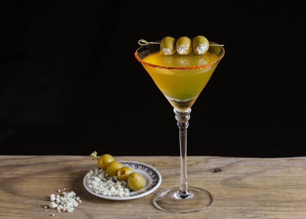 A glass of dirty martini served with olives and salt.