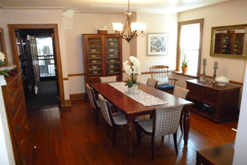 This is the dining room with a large wooden dining table that blends well with the hardwood flooring and the display cabinet on the far side. These are then complemented by the simple chandelier hanging from the beige ceiling. Image courtesy of Toptenrealestatedeals.com.