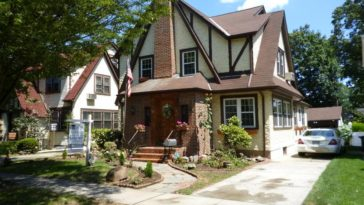 This is the front view of the Tudor-style brick house with dark brown accent that extends to the roof. These view also showcases the warm welcome of the main door adorned with shrubs. Image courtesy of Toptenrealestatedeals.com.