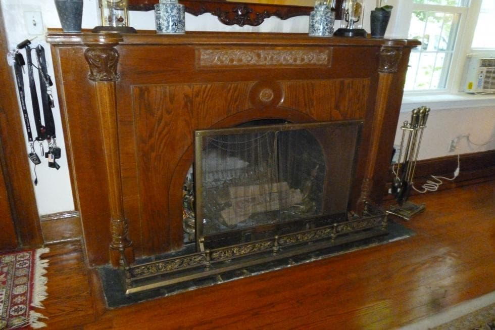 This is a closer look at the fireplace of the living room with a dark wood mantle that pairs well with the hardwood flooring. Image courtesy of Toptenrealestatedeals.com.