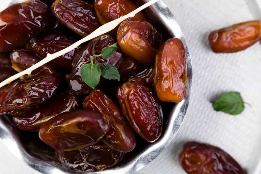 Dried dates served in a garnished silver bowl.