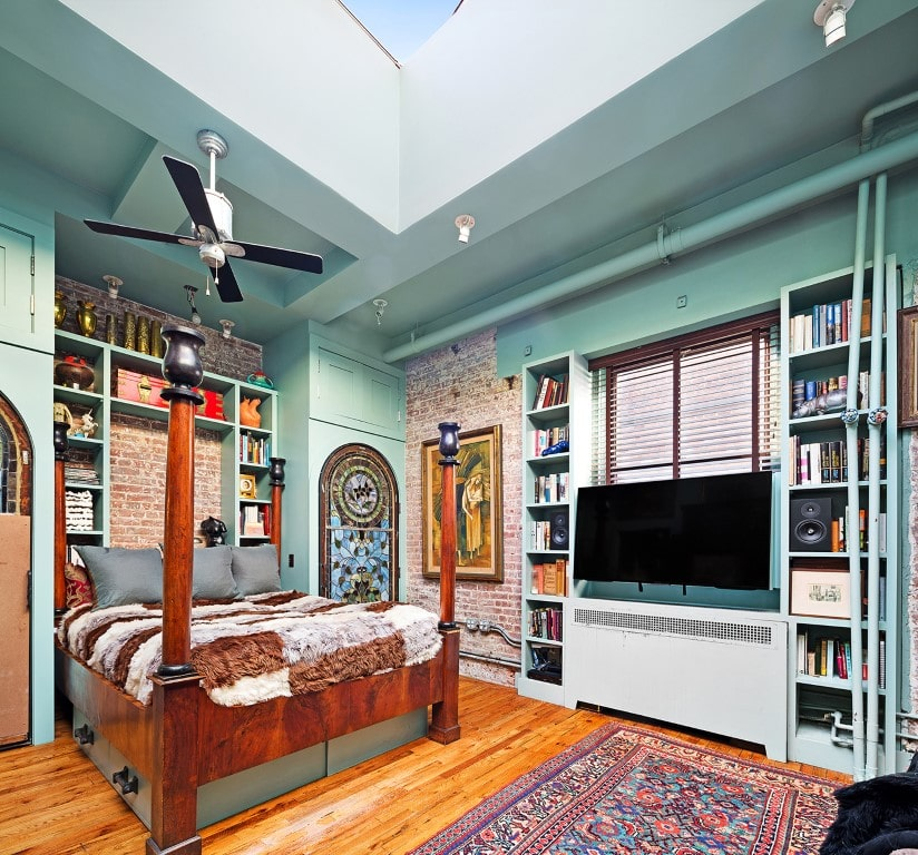 This is the bedroom with a large four-poster wooden bed, green walls with built-in shelves and a skylight that brings in natural lighting. Image courtesy of Toptenrealestatedeals.com.