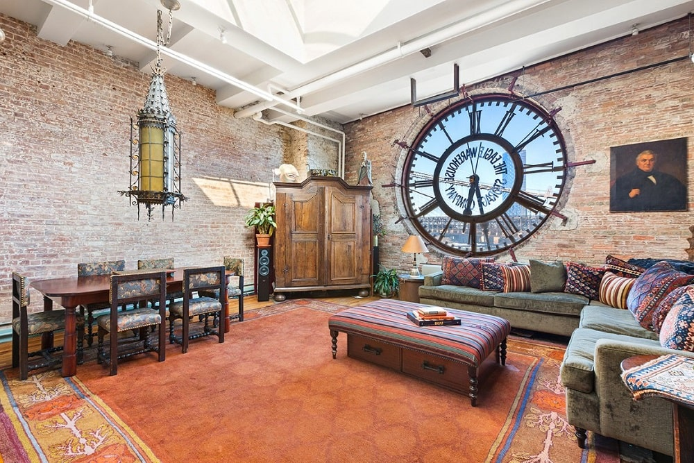 This is the great room of the loft that houses the dining area on the left and the living room area on the right. These are all complemented by the large clock face and the tall red brick walls. Image courtesy of Toptenrealestatedeals.com.