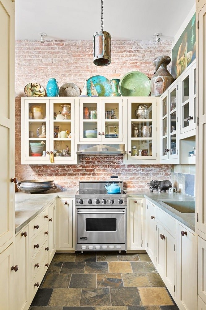 This is a look at the long and narrow kitchen with beige cabinetry to complement the red brick walls. These makes the stainless steel appliances stand out. Image courtesy of Toptenrealestatedeals.com.