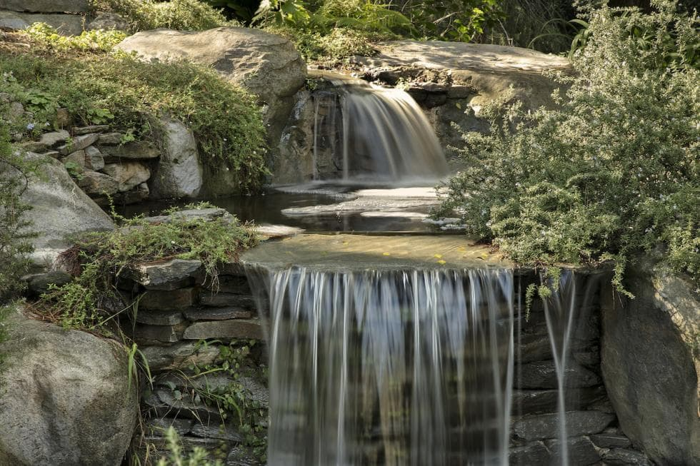 This is a close look at the landscaping of the estate with a waterfalls display made to look natural with shrubs and moss. Image courtesy of Toptenrealestatedeals.com.