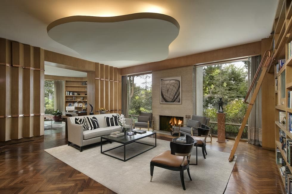 This is the spacious living room with a sofa set by the stone fireplace across from the built-in bookshelves. Image courtesy of Toptenrealestatedeals.com.