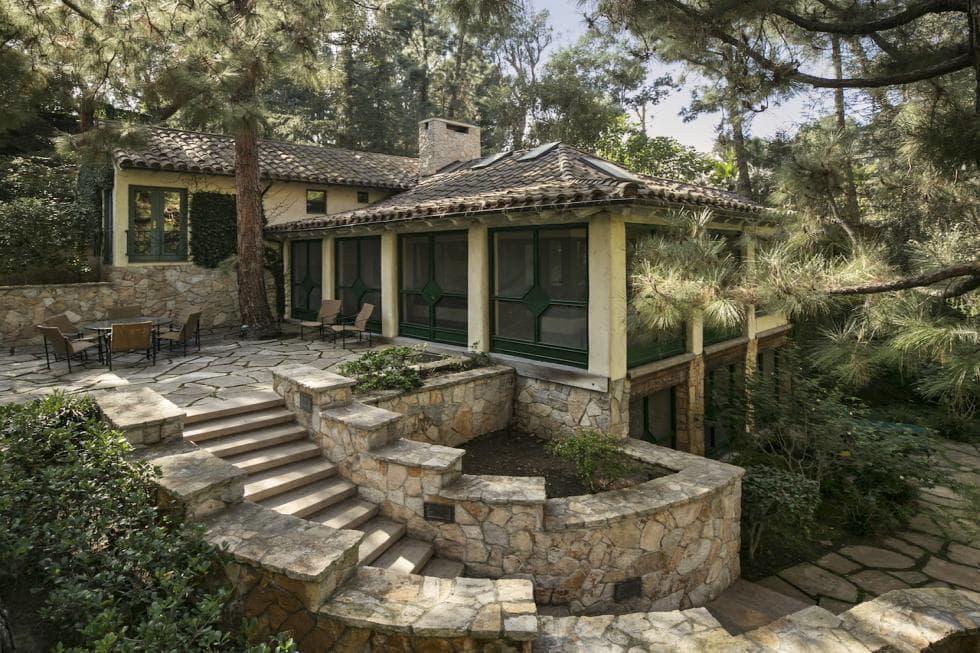 This is a look at the side of the house with mosaic stone walls and walkways that lead to a set of stone steps up to the outdoor dining area on the side of the house under the shade of tall trees. Image courtesy of Toptenrealestatedeals.com.