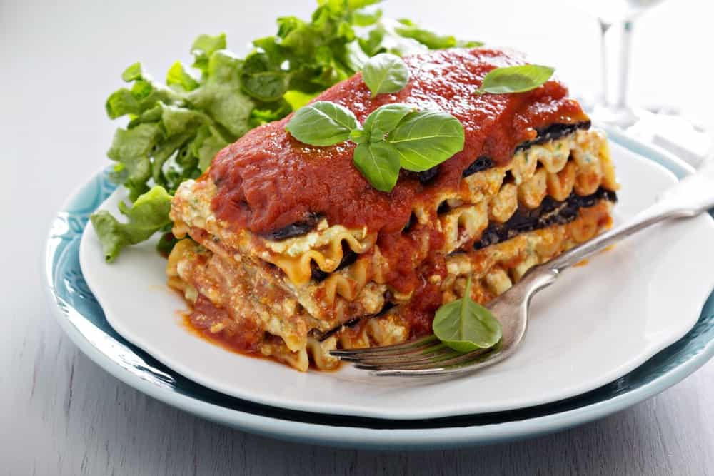 A serving of eggplant lasagna topped with parsley.