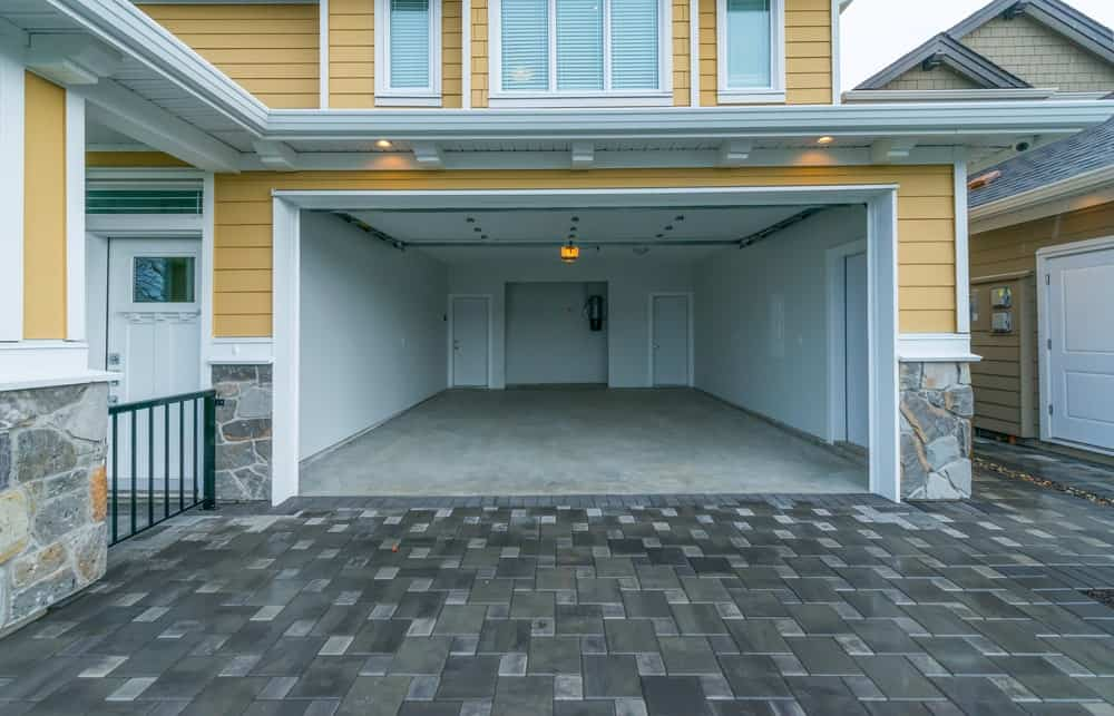 A look at an empty garage with roll-up garage doors, white walls and white ceiling.