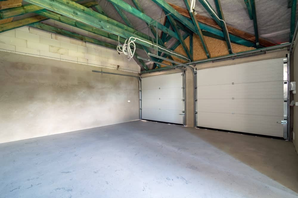 A look at an unfinished two-car garage with roll-up garage doors.