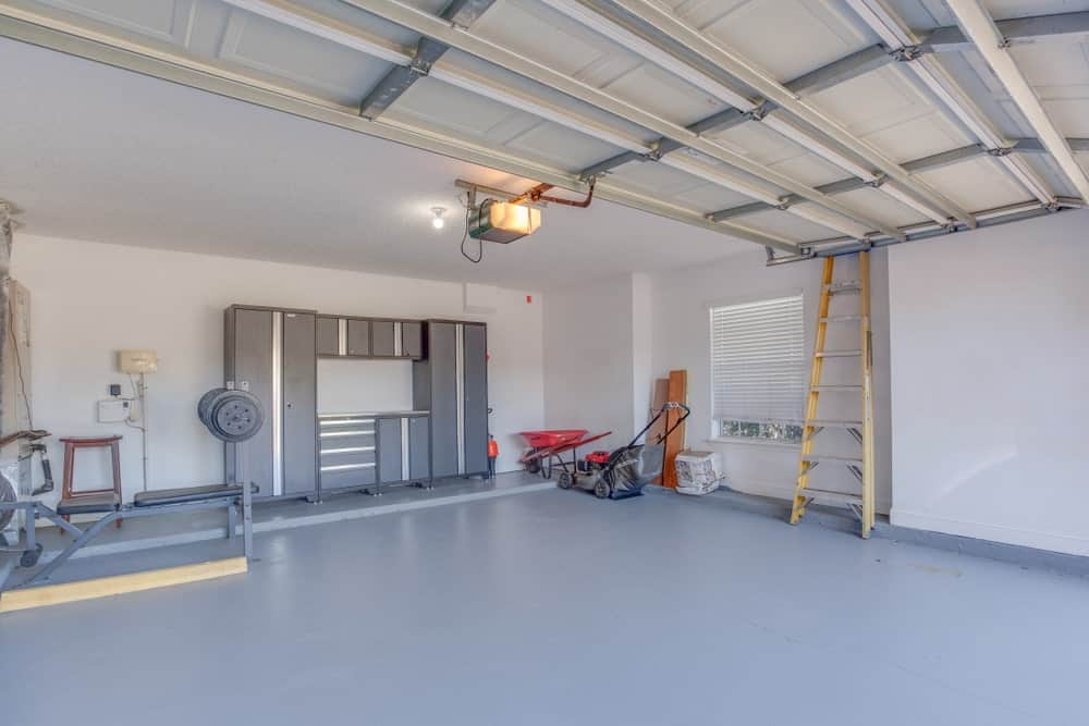 A bright spacious garage with white walls, white ceiling and gray flooring.