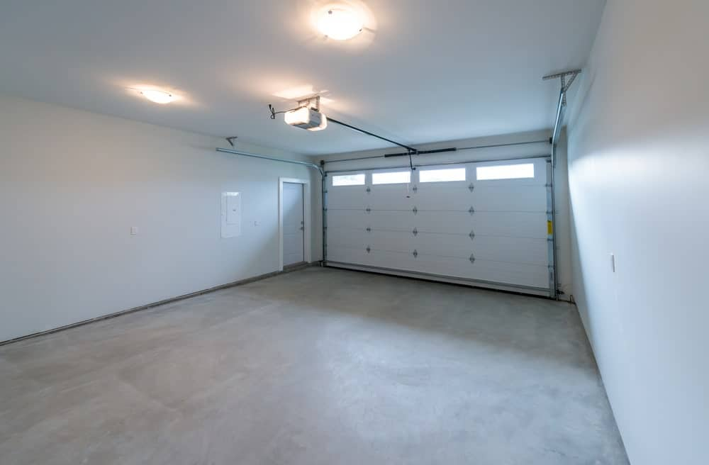 A close look at a spacious empty garage with finished floor, walls and ceiling.