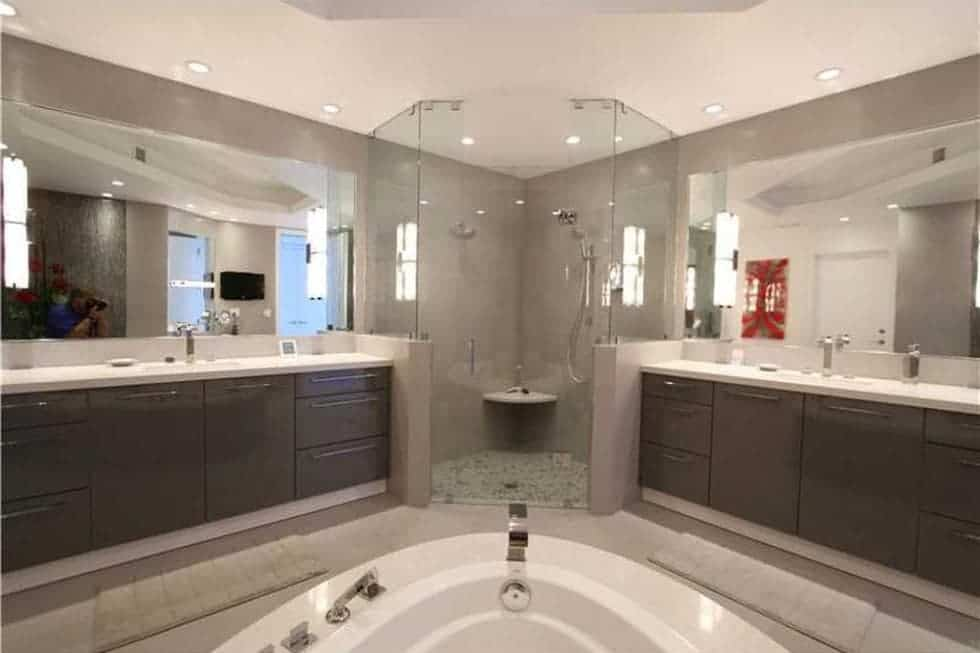 This is the spacious bathroom with a couple of vanities flanking the glass-enclosed shower area at the corner. Image courtesy of Toptenrealestatedeals.com.