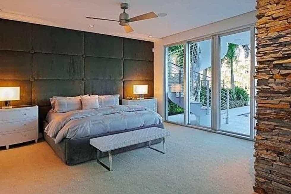 This bedroom has a cushioned black wall that serves as a large headboard for the bed that is flanked with bedside drawers and table lamps. Image courtesy of Toptenrealestatedeals.com.