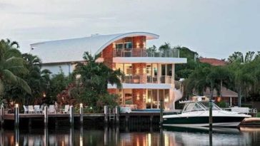 This is an exterior look at the waterfront house from the vantage of the water. You can see here that it has expansive glass walls and a large dock complemented by tall tropical trees. Image courtesy of Toptenrealestatedeals.com.
