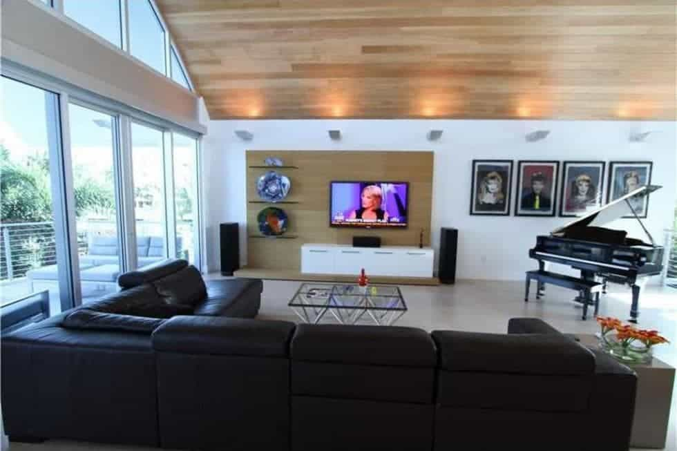 This other view of the living room shows the wall-mounted TV across from the L-shaped sectional sofa. On the side of this is the grand piano. Image courtesy of Toptenrealestatedeals.com.