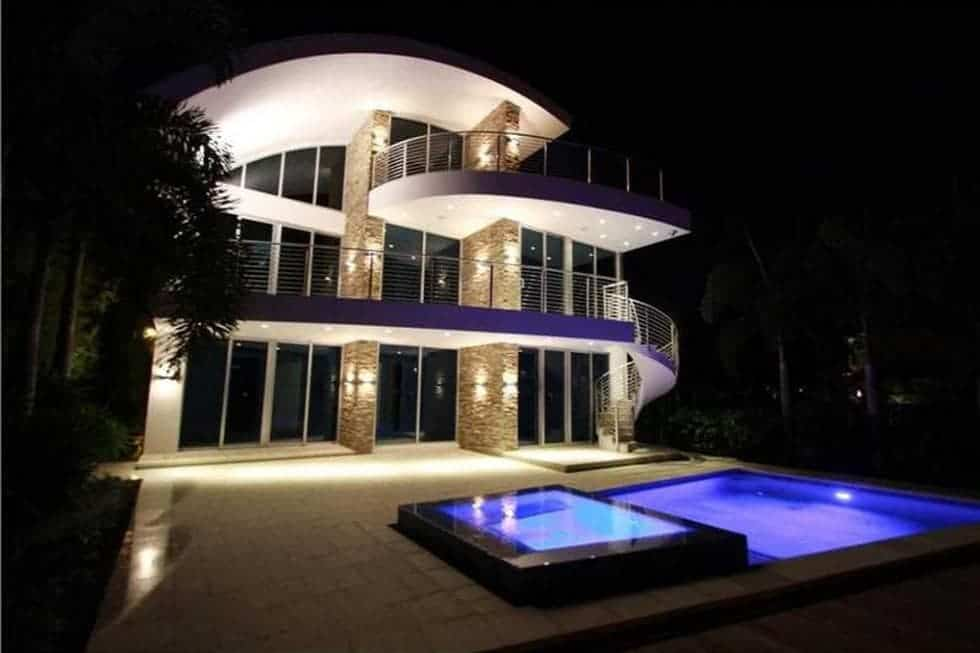 This is a nighttime view of the house showcasing the warm exterior lights of the house and the ethereal glow of the swimming pool and spa. Image courtesy of Toptenrealestatedeals.com.