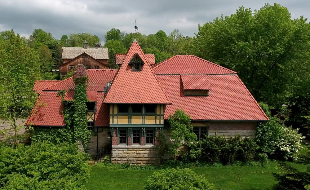 This is a look at the back of the main house with a red roof and stone exterior walls complemented by the green landscape. Image courtesy of Toptenrealestatedeals.com.