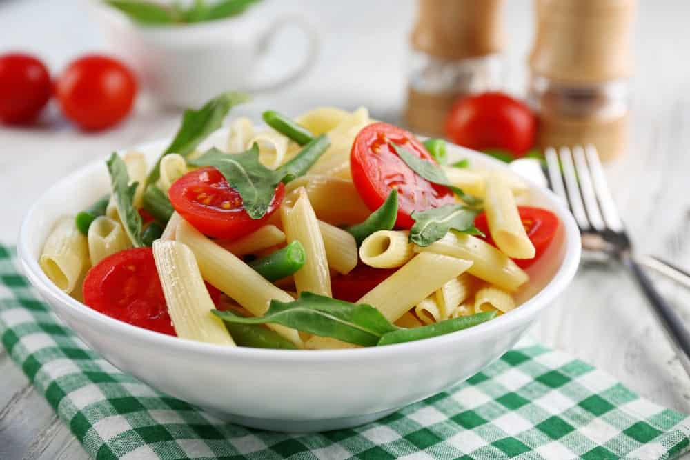 A bowl of French bean pasta with arugula and tomatoes.