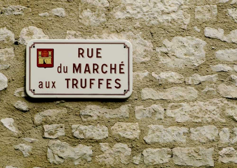A sign to the French truffle market against the stone wall.
