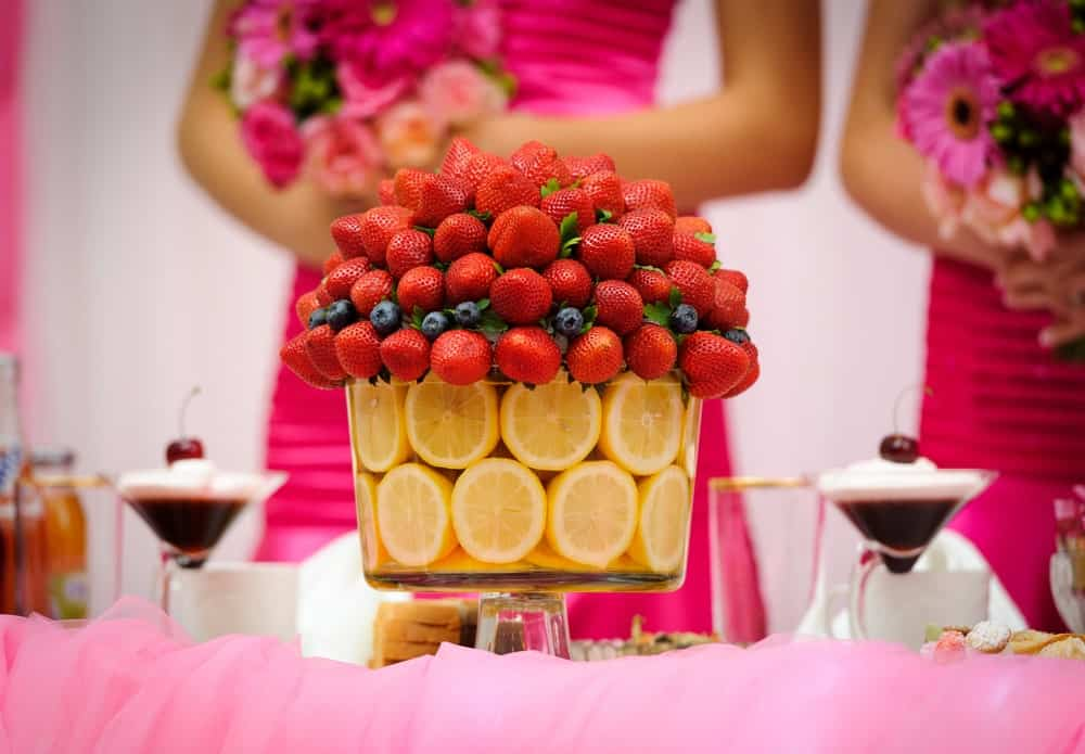 Strawberries, blueberries, and slices of lemons on a cake tray featured on a wedding reception.