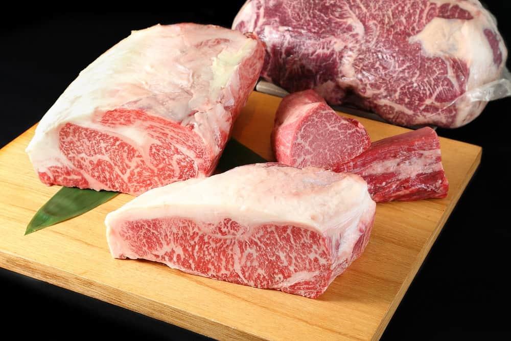 Sliced Wagyu tenderloin steak on a wooden chopping board.