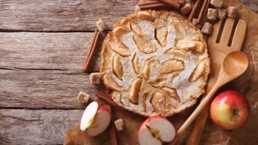 A freshly baked German apple pancake on a wooden table.