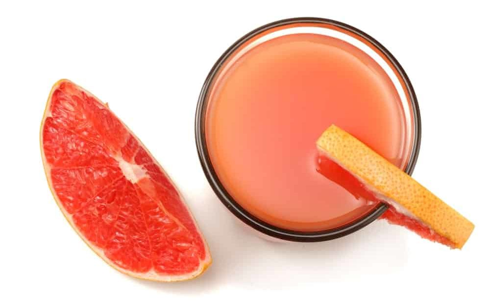 Top view of a grapefruit juice with a slice on the side.