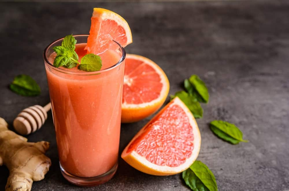 Grapefruit smoothie with slices of grapefruit and a ginger on the side.