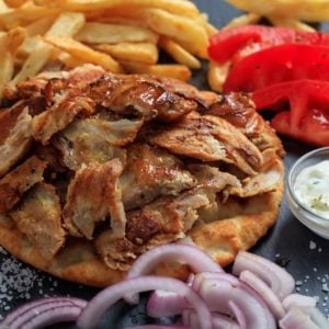 A freshly-made Greek gyro with a side of fries, fresh tomatoes, onions and dressing.