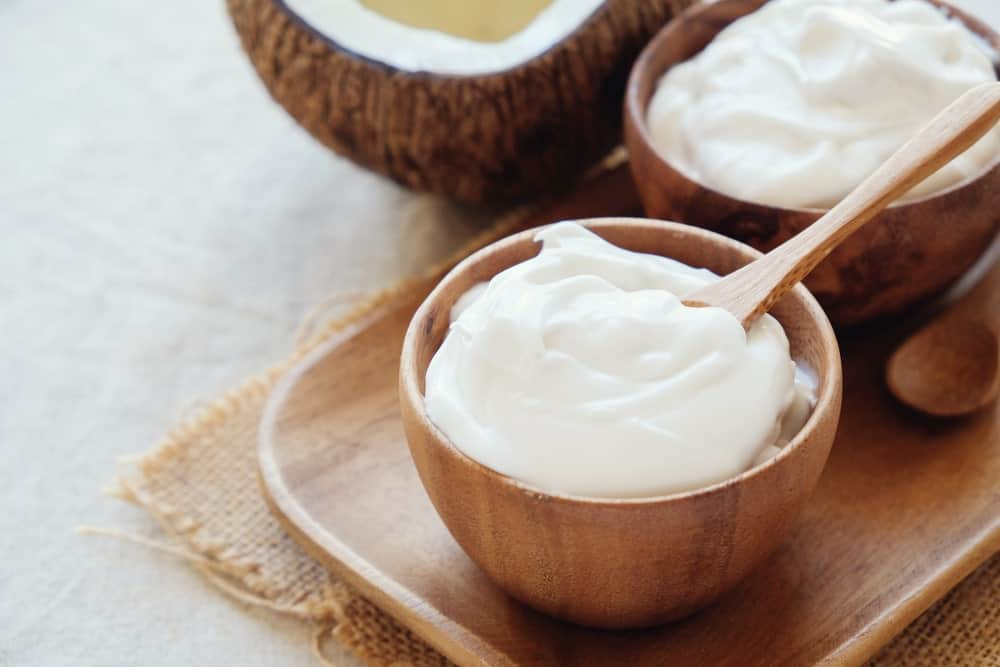 Bowls of Greek yogurt with a coconut on the side.