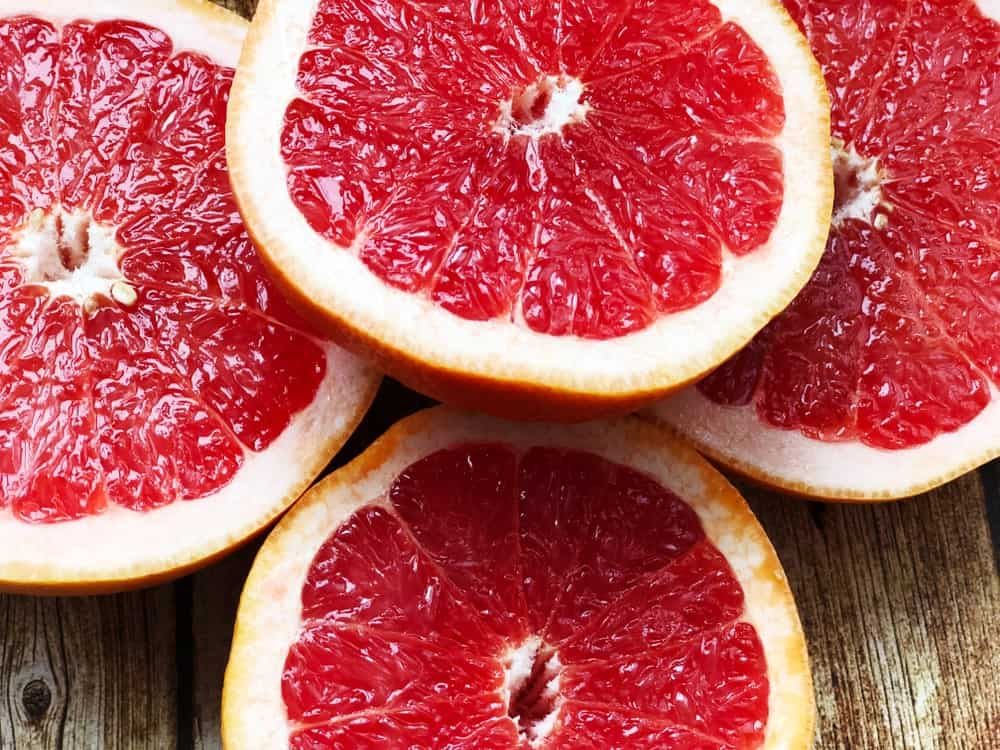 Slices of grapefruits on wooden background.